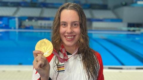 Aurélie Rivard montre fièrement sa médaille et tient son bouquet devant la piscine du Centre aquatique de Tokyo.