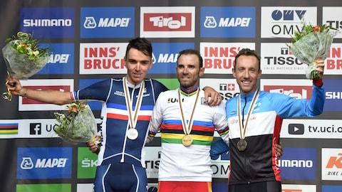 Le Canadien Michael Woods (à droite, bronze), sur le podium des Championnats du monde sur route, à Innsbruck, aux côtés du Français Romain Bardet (argent) et de l'Espagnol Alejandro Valverde (or)