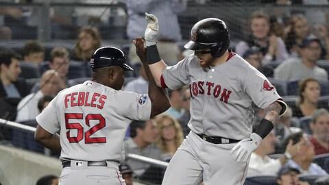 Christian Vazquez (à droite), des Red Sox de Boston, célèbre son circuit en solo avec l'instructeur Carlos Febles.