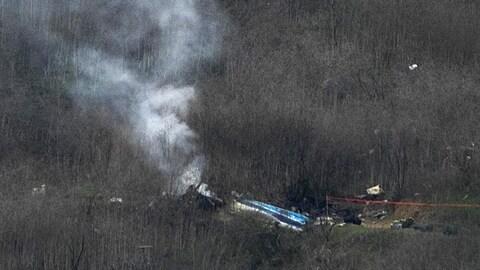 L'hélicoptère est écrasé au beau milieu d'une fo^rt, et de la fumée s'en échappe.