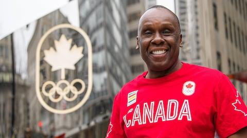 Il est de devant le logo du Comité olympique canadien.