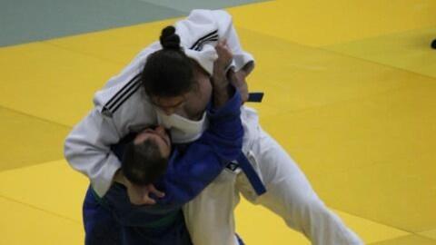 Deux judokas luttent, et tentent de faire tomber au sol leur adversaire.