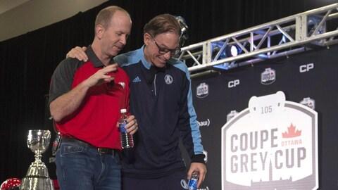 Marc Trestman passe son bras autour du cou de Dave Dickenson alors que les deux entraîneurs quitte la scène après leur rencontre avec les médias.