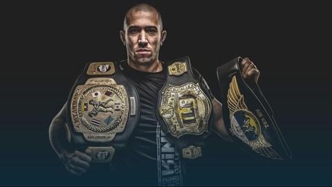 Dave Leduc montre ses trois ceintures de champion.