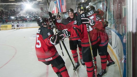 Les joueurs de l'Équipe Canada-Est célèbrent dans le coin de la patinoire après avoir marqué un but.