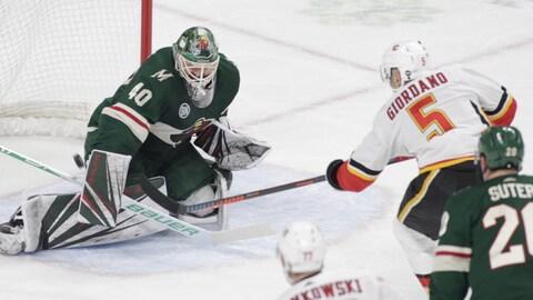 Mark Giordano, des Flames de Calgary, tente un tir du côté rapproché contre le gardien Devan Dubnyk, du Wild du Minnesota.