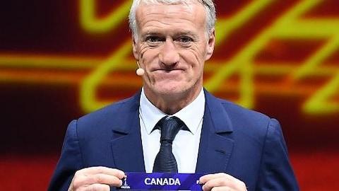 Il tient du bout des doigts l'affichette du Canada.