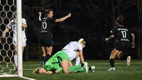 Elle lève les bras en l'air pour célébrer son but avec une coéquipière, tandis que trois adversaires sont dépitées.