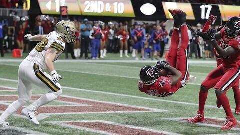 Deion Jones tombent sur le dos après avoir intercepté le ballon.