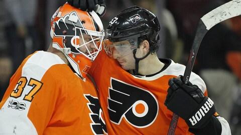 Brian Elliott et Shayne Gostisbehere célèbrent après la victoire des Flyers.