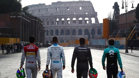 Quatre pilotes marchent en direction du Colisée.