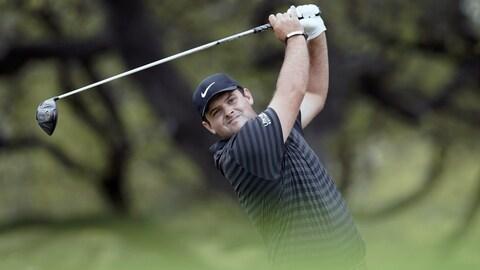 Patrick Reed frappe sa balle au départ du huitième trou au cours de son match contre Jordan Spieth au Championnat du monde de golf par trous.