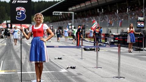 Une jolie jeune femme vêtue d'un costume traditionnel autrichien pose fièrement en tenant un panneau indiquant le nom du pilote Daniel Ricciardo et le numéro de son couloir (3).