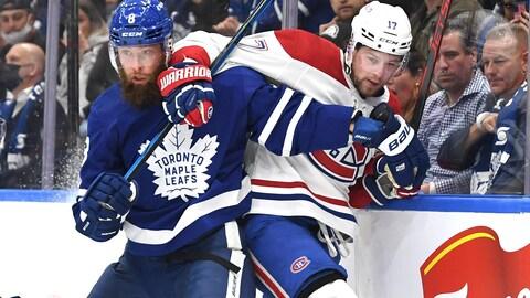 Le défenseur des Leafs Jake Muzzin plaque l'attaquant du Canadien Josh Anderson le long de la bande.