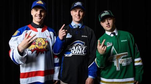 Trois joueurs de hockey font signe de la main pour montrer leur rang de sélection