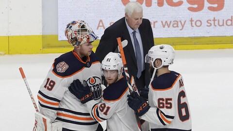 Ken Hitchcock déambule sur la glace de San José après sa première victoire avec les Oilers, alors que Drake Caggiula, Mikko Koskinen et Cooper Marody célèbrent leur succès.