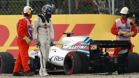 Lance Stroll regarde sa voiture près sa sortie de piste durant la séance de qualification du Grand Prix d'Espagne.