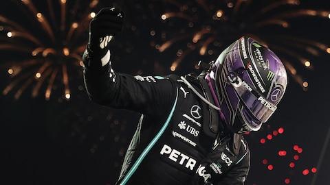 Lewis Hamilton, casqué, en combinaison noire, lève le bras droit, il y a des feux d'artifice derrière lui.