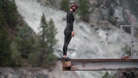 Elle se tient debout au bord d'une plateforme, prête à plonger.