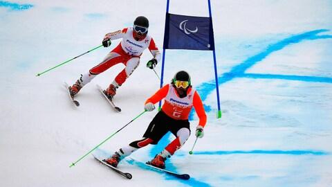 Mac Marcoux suit son ancien guide Robin Femy pendant un épreuve de paraski alpin, aux Jeux paralympiques de Sotchi, en 2014.
