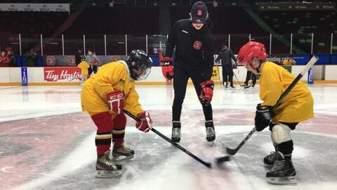 Marco Rossi dépose une rondelle géante sur une patinoire pour des enfants aveugles qui jouent au hockey sonore