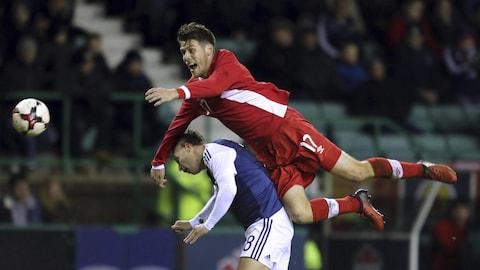 Maxim Tissot saute au-dessus d'un défenseur écossais pendant un match amical entre le Canada et l'Écosse en 2017.