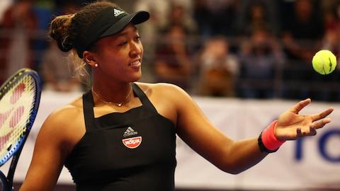 Naomi Osaka lance la balle pendant un match du tournoi de Tokyo