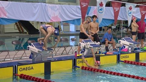 Une nageuse s'apprête à plonger lors d'un entraînement à la piscine du Centre sportif Kinsmen d'Edmonton