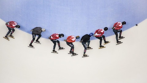 Sept patineurs prennent un virage sur la glace.