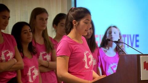 Une jeune femme parle au lutrin devant ses collègues.