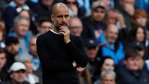 L'entraîneur de Manchester City est songeur sur les lignes de côté lors d'un match.
