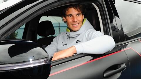 Rafael Nadal souriant au volant d'une voiture.