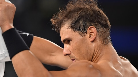 Rafael Nadal se change sur le bord du terrain.