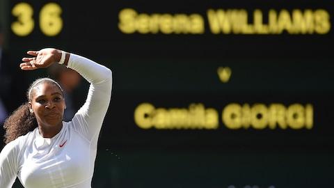 Elle salue le public après une victoire à Wimbledon.
