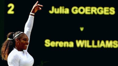 Serena Williams lève le bras gauche après sa victoire face à Julia Görges à Wimbledon.