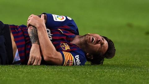 Lionel Messi, du FC Barcelone, se tient le bras après une lourde chute au cours de laquelle il a subi une fracture, en première mi-temps d'un match contre Séville.