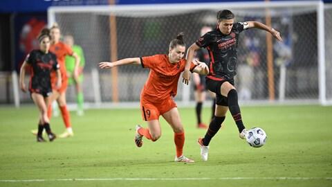 Deux joueuses bataillent pour la possession du ballon lors d'un match de la NWSL.