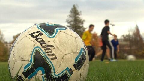 un ballon de soccer et derrière des enfants qui jouent