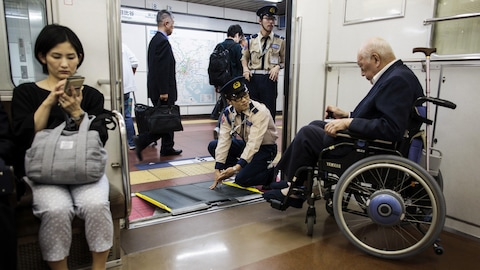 Une personne âgée japonaise est aidée à sortir du métro de Tokyo par deux employés.