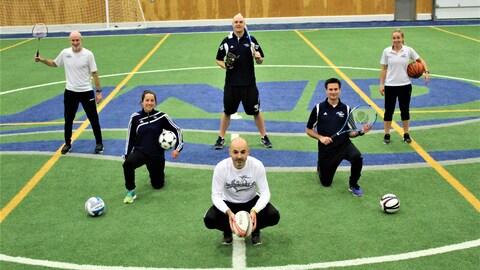 Six enseignants d'éducation physique sur un terrain couvert.