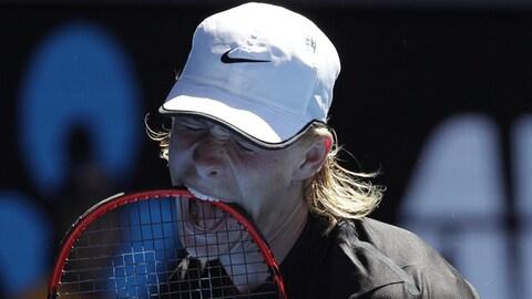 Denis Shapovalov, frustré, mord sa raquette au cours de son match de deuxième tour contre Jo-Wilfried Tsonga aux Internationaux d'Australie.