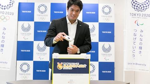Ryunosuke Haga, médaillé de bronze en judo aux Jeux de Rio, en 2016, dépose dans une boîte de collecte lors d'un événement du comité organisateur des Jeux de Tokyo 2020.
