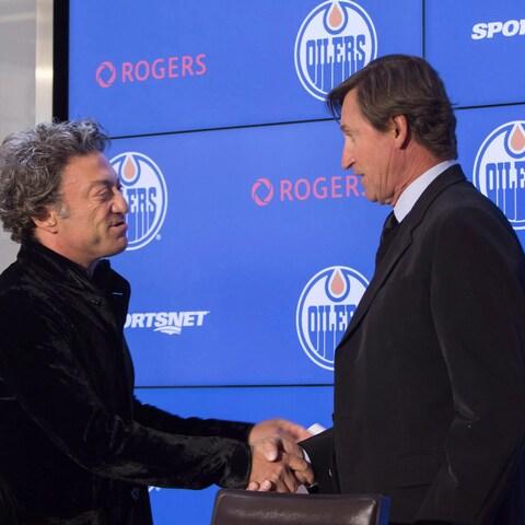 Daryl Katz serre la main de Wayne Gretzky lors d'une conférence annonçant le retour de la Merveille au sein de l'organisation des Oilers.