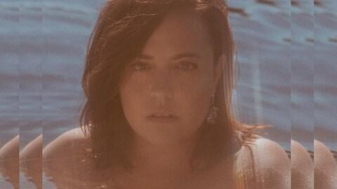 La chanteuse Ariane Moffatt, dans une piscine, ses épaules et sa tête sorties de l'eau.