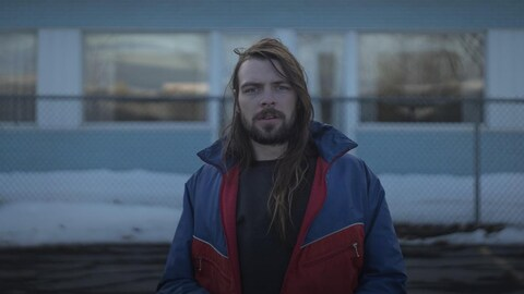 Dave Chose, à l'extérieur, dans un stationnement. Une clôture en maille de chaînes se trouve derrière lui au fond de la cour, devant un immeuble bleu et blanc vitré. Il y a de la neige au sol.