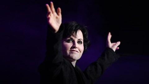 Delores O'Riordan, chanteuse des Cranberries, toute de noire vêtue, qui tend les bras en guise de salut