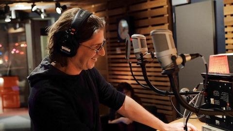 Jean-René Dufort sourit au micro dans le studio 85 de Radio-Canada