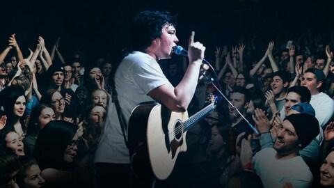 L'artiste chante sur scène face à un large public.