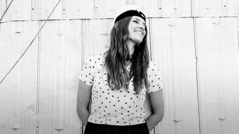 Photo noir et blanc : la chanteuse Émilie Clepper se tient tout sourire devant le mur en tôle d'un bâtiment.