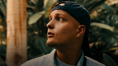 Le rappeur FouKi, casquette à l'envers, visage légèrement de profil, devant une végétation tropicale.